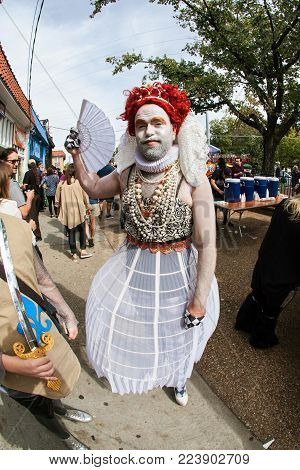 ATLANTA, GA - OCTOBER 2017:  A man dressed like the Queen of Hearts from Alice in Wonderland fans himself waiting for the start of the Little Five Points Halloween parade in Atlanta, GA on October 21, 2017.