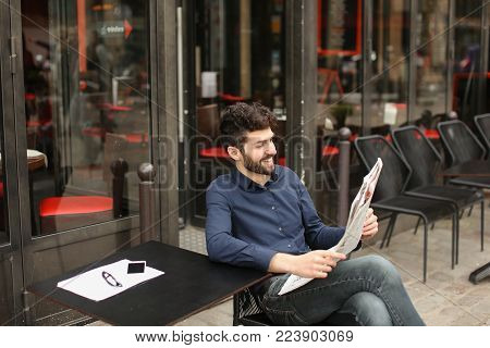 journalist enjoying with reading newspaper columns and articles with close up face in  . Gladden man smiling and resting. Concept of popular public press Mass Media information.