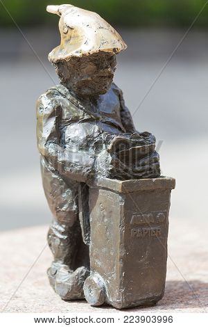 WROCLAW - POLAND, JUNE 13, 2017: Wroclaw dwarf, small fairy-tale bronze figurine on the sidewalk,  Wroclaw, Poland. There are over 350 dwarfs spread all over the city, they are a big tourist attraction