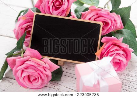 Small blank chalkboard for Valentine's, mother or woman day. Background with pink roses on old wooden table.