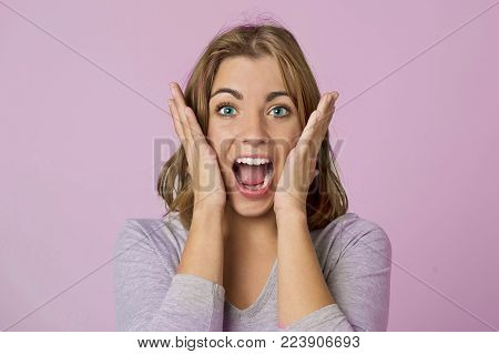portrait of young pretty and attractive blond Caucasian girl with beautiful blue eyes on her 20s excited and happy with mouth opened in nice shock and surprise face expression isolated in pink background