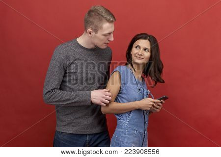 Young beautiful couple standing on a red background. Brunette girl texting on the phone, trying to hide the correspondence. The blond man trying to catch his beloved