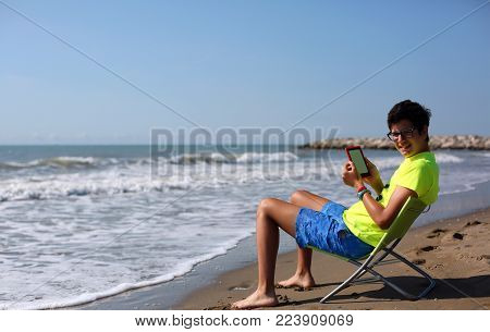 Young Boy Reads Ebook And Shorts On The Beach With Vintage Effect