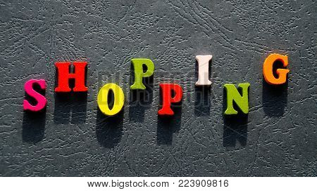 The word SHOPPING made of colored wooden letters on the table the dark color.