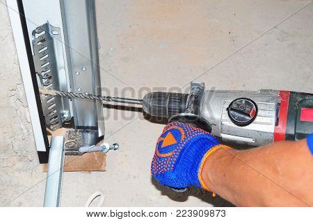 Contractor  repair and install garage door with drilling machine. Replace a Broken Garage Door Spring.