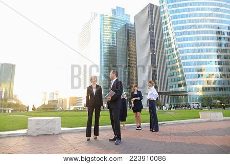 Business employees talking with boss in La Defense Paris keeping laptop and document cases. Concept of successful management team members. Cheerful biz partners resting outside and speaking about good results.