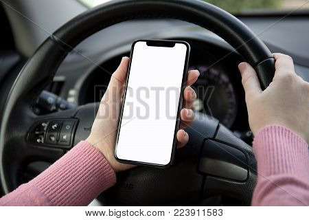 women hands holding phone with isolated screen in the car