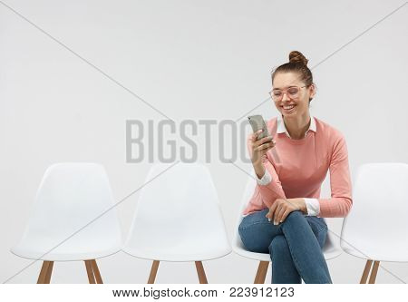 Woman wearing eyeglasses and casual pink sweater sitting in the line, holding smartphone texting sms. Busy woman sitting on chair indoors