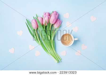 Coffee cup and pink tulip flowers on pastel background top view. Beautiful spring breakfast on Mothers or Womans day. Flat lay.