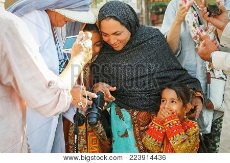 Iran, Yazd, old town - September 19, 2016:  Local family communicates with foreign tourists on the street