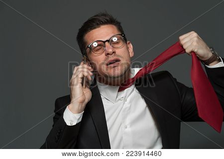 Stress at work. An upset businessman talks on the phone about ruptured deal and is ready to hang himself on tie showing suicide on gray background