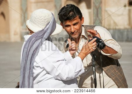 Iran, Yazd, old town - September 19, 2016:  Local man communicates with foreign tourists outdoors.