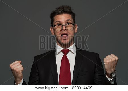 Disheveled young man the manager in formal suit is pleased with unexpected success on gray background