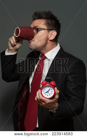 The dinner is over. Young male manager in formal attire and glasses drinks his coffee and holds clock showing the ending time on a gray background