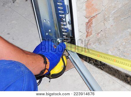 Contractor installing garage door and with measuring tape