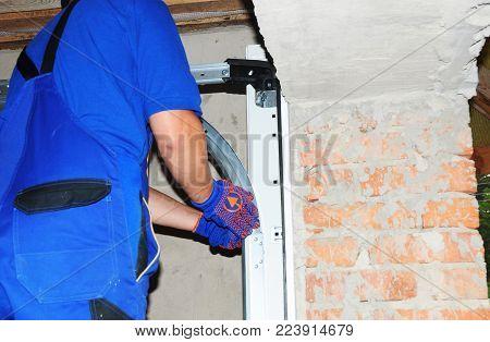 Contractor Installing Garage Door With Measuring Tape. Install Garage Door Opener Springs System.