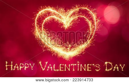 Beautiful greeting card Happy Valentines Day. Sparkling golden words Happy Valentine's Day and Two glowing heart on a red festive background. Holiday Wide screen Web banner
