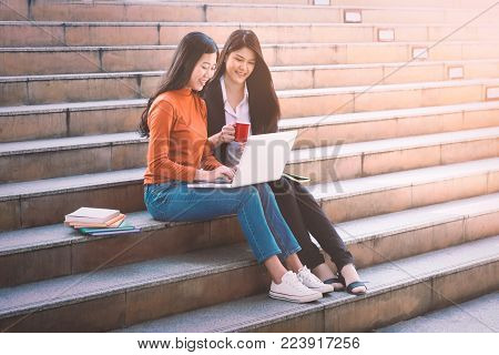 Asian college student using labtop lerning online on campus. - Education concept