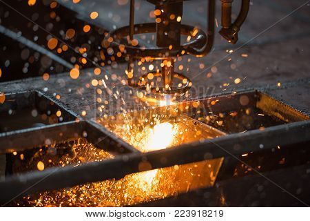 Acetylene torch CNC auto machine cutting steel plate metalwork  with bright sparks in factory.