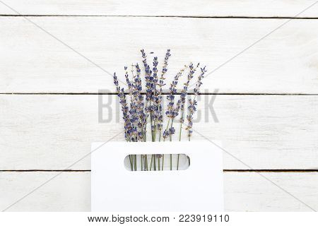Bouquet of lavender in a paper white package on a wooden background. Flat lay