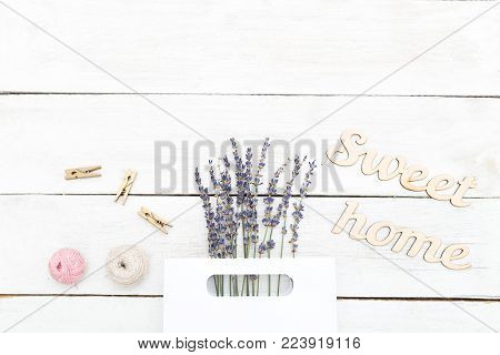 Abouquet of lavender in a paper bag and a wooden inscription sweet home. Flat lay