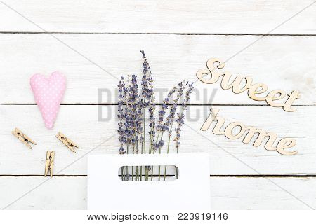 A bouquet of lavender in a paper bag and a wooden inscription sweet home. Flat lay