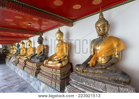 Several old Buddha statues with cloths at the Wat Pho (Po) temple complex in Bangkok, Thailand.