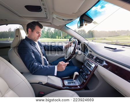 Businessman using cell phone and texting while driving not paying attention to the road. Dangerous texting and driving at the same time