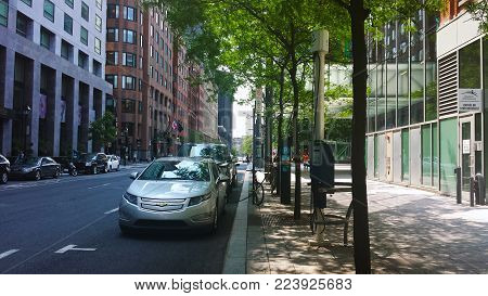 Montreal, Quebec, Canada - 20 July 2016: Electric cars charging at recharging station undert green trees in summertime as editorial