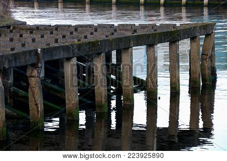 Disused old coastal concrete jetty moorings structure
