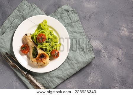 Green pasta with spinach and baked chicken leg