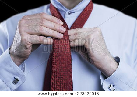 Close up of a businessman tying knot on red tie, getting ready