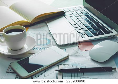 Close up of office desktop with blank smartphone, business report, open organizer and other items. Technology and accounting concept