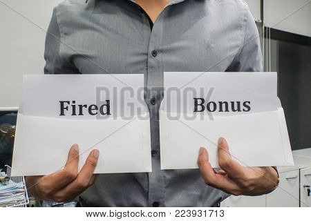 business concept - businessman hold fired and bonus sign for working performance