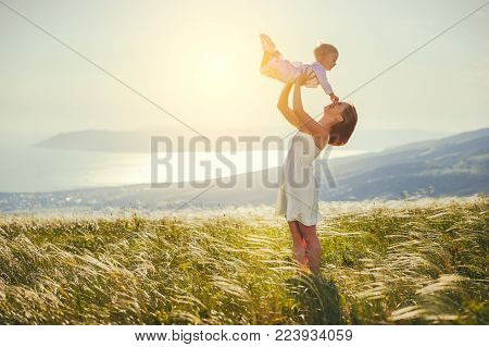Happy family mother and baby son laughing and playing in nature