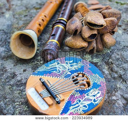 Close up of kalimba, rattle, flute and horn pipe music instruments on a big stone.