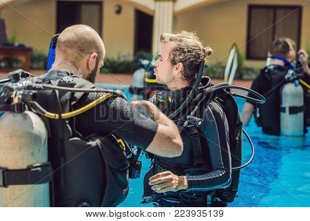Diving Instructor And Students. Instructor Teaches Students To Dive