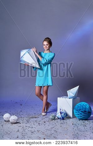 Fashion kid. Pretty girl in an elegant blue dress for teenage girls with a make-up. Origami and minimalism. Designer collection. Charming teenager girl in studio holds an origami figure.