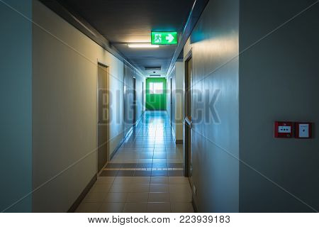 Fire exit sign and fire exit door in building corridor.