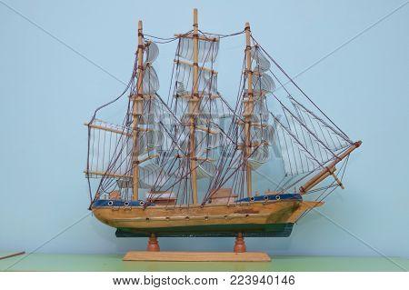 Sailing ship model in souvenir shop, closeup. Handmade sailboat miniature in gift market. Showcase with frigate figurine . Sailing ship of the VI century galleon, model of the ship.