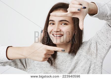 Tender and sincere caucasian girl with cheerful smile and warm look, making frame gesture with hands while standing next to white wall. Young vlogger plans how to shoot her new project.