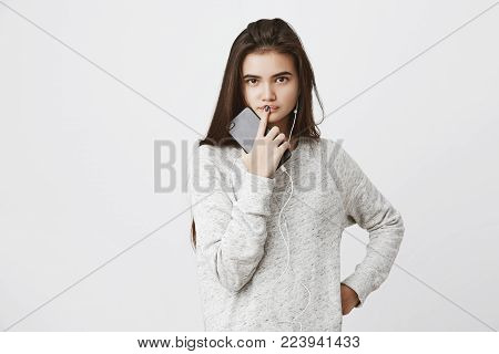 Waist up portrait of attractive european female holding phone in hand while touching lips with index finger, expressing curiosity and eagerness to know answer, isolated over white background.