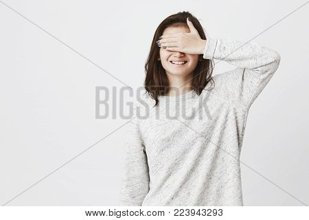 Studio shot of young cute european girl, covering her eyes with hand while smiling cheerfully, being impatient. Mom told not to look as father takes out surprise present for her. Emotions concept