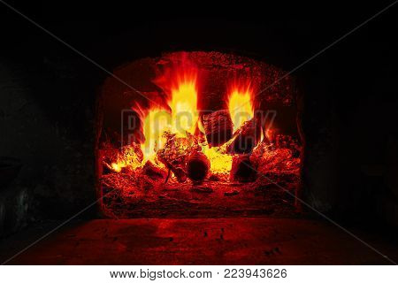 Firewood burning in brick oven, fire flame closeup. Flame on burning wood in stone fireplace from firebricks