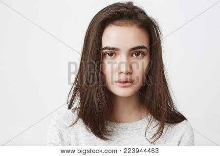 Close up studio shot of tired, exhausted young teenage girl, who is looking at camera with fed up look and half-opened mouth. Newcomer tired of listening customers complaints. Copy space