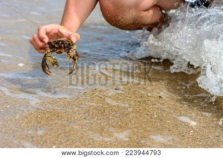 The waves wash the body of a man with a crab in his hands, a photo taken with the camera's short exposure