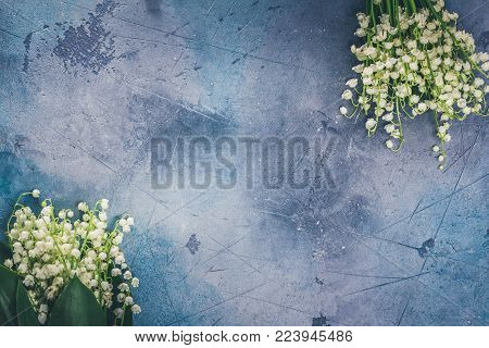 Lilly of the valley flowers for Mothers Day on gray stone background with copy space, retro toned
