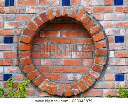 Round brick frame in wall, with ceramic blue tile highlights. Circular brick wall frame inclusion. Classic vintage paved bricks with mortar and ceramic blue tile highlights. Green plants at bottom.