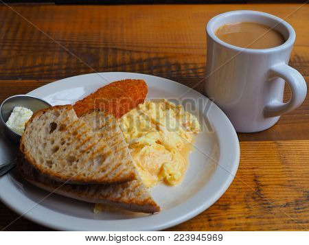 Breakfast of wet soft scrambled eggs. Wet scrambled eggs, sour dough toast, hash brown and a coffee. White plate on a vintage solid wood table.