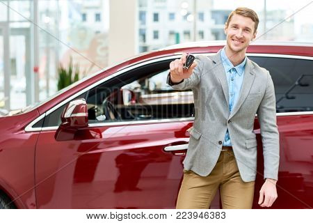 Portrait of handsome young man smiling happily at camera standing by brand new luxury car in showroom and presenting car keys, copy space